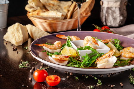 The concept of Italian cuisine. Tiger prawns on rice chips in a creamy sauce. Arugula salad and lemon. On the table is a glass of red wine. beautiful serving in the restaurant Stock Photo