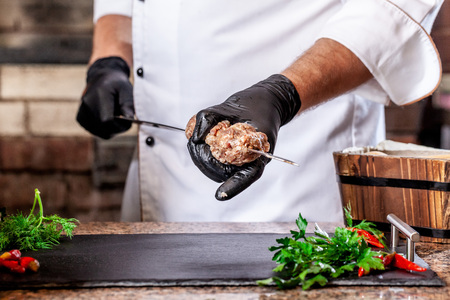 The concept of Georgian cuisine. Recipe for cooking meat lyulya kebab in the dough on the grill. Chef puts meat on a skewer.