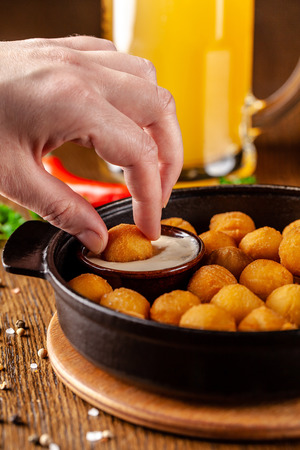Czech cuisine concept. Potato croquettes. Balls of mashed potatoes, breaded, deep-fried in a cast iron pan. Served with raw sauce. Snack to beer.