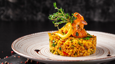 The concept of Spanish cuisine. Paella with seafood, shrimps, squid and greens. Beautiful serving in the restaurant. Stockfoto