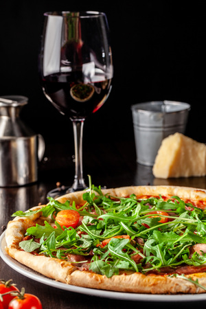 The concept of Italian cuisine. Pizza with sausage salami, bacon, cherry tomatoes and arugula. Next to the table is a glass of red wine. Beautiful serving dishes in the restaurant. Zdjęcie Seryjne