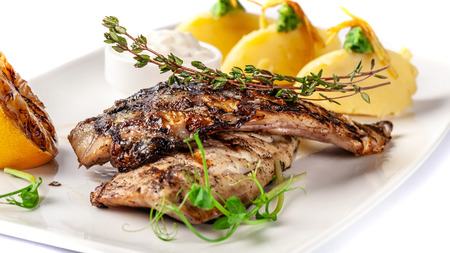 Grilled juicy mackerel, served with mashed potatoes, lemon, and tartar sauce. Microgreen. Modern pitch on a white tarekle. On a white background. beautiful serving in the restaurant.