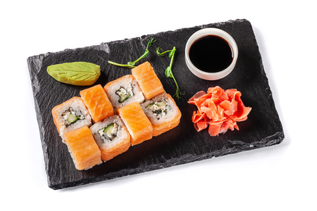 The concept of Japanese cuisine. Rolls with salmon, feta cheese, cucumber. Near soy sauce, ginger and wasabi. Modern serving dishes in the restaurant on a black slate blackboard. On a white background