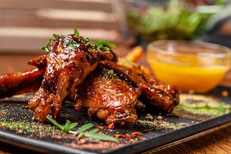 The concept of Indian cuisine. Baked chicken wings and legs in honey mustard sauce. Serving dishes in the restaurant on a black plate. Indian spices on a wooden table. background image. Stock fotó