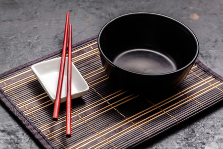 Empty Japanese dishes. A black ceramic bowl for Chinese noodles or Thai soup lies on a bamkuk rug. White saucepot for soy sauce and red Chinese sticks on a black background. Top view, copy space