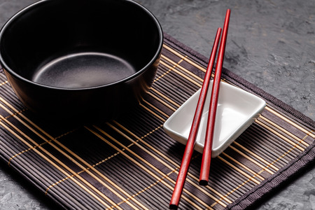 Empty Japanese dishes. A black ceramic bowl for Chinese noodles or Thai soup lies on a bamkuk rug. White saucepot for soy sauce and red Chinese sticks on a black background. Top view, copy space Standard-Bild