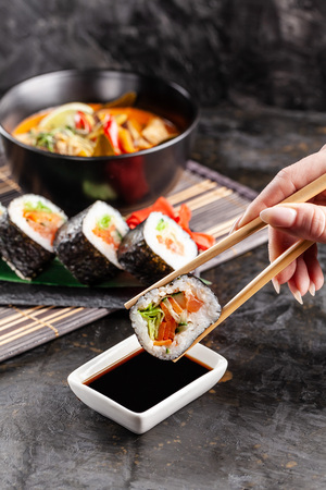 Concept of Asian cuisine. The girl is in a Chinese or Japanese restaurant sushi, holds wooden sticks in his hands. Dunk sushi in soy sauce. Different Asian dishes are on the table
