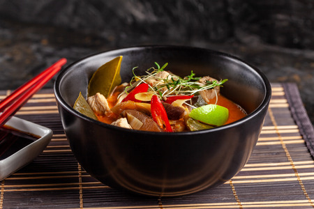 Concept of Asian cuisine. Thai soup Tom yam of chicken broth and coconut milk, mushrooms, chicken, chilli peppers, and vegetables. Japanese dish in black. Top view, copy space