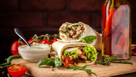 Mexican cuisine, burrito with chicken, cherry tomatoes, lettuce, mushrooms, rucola and chili peppers, on a black background. With salsa sauce. Copy space, selective focus