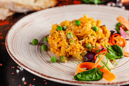Concept of Spanish cuisine. Paella with seafood and shrimps, with green peas in a clay plate. A glass of cool wine is on the table. background image, copy space