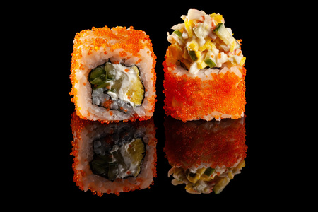 Concept of Asian cuisine. Two rolls of sushi with different fillings on a black background with the age for a Japanese menu for a cafe, restaurant, sushi bar.