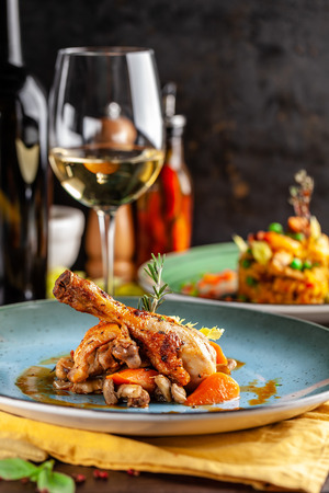 Concept of Italian cuisine. Stewed chicken in strong wine with vegetables. Serving dishes in a restaurant in a blue plate. White wine sherry in a glass on the table. Copy space
