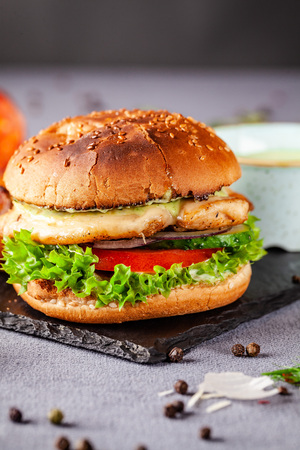 American burger with chicken cutlet, tomato, cucumber, green sauce. Sauce and for french fries on a black stone slate board. Dish in a fast food restaurant. Copy space