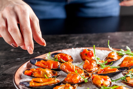 European cuisine. Marinated mussels in tomato sauce with rosemary, garlic, chili. Serving dishes in the restaurant on a plate with coarse sea salt on a black background. Copy space