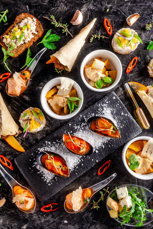 European cuisine. Appetizer for wine on a black background. Pate, mini salad, canape, sea products, salmon and mussels in tomato sauce. Top view, copy space 免版税图像