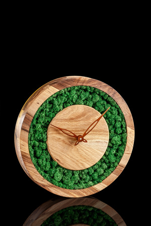 Wooden clock with color stabilized moss on a black background with mirror otgruzheniya. Trend 2019. Wall Clock. copy space
