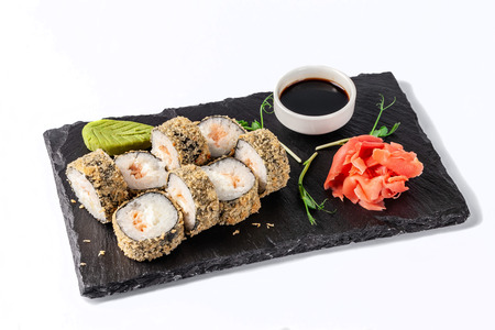 Concept of Japanese cuisine. Deep fried roll with salmon and mayonnaise in Panko bread crumbs. Near soy sauce, ginger and wasabi. Modern serving dishes in the restaurant on a black slate blackboard.  Stock Photo