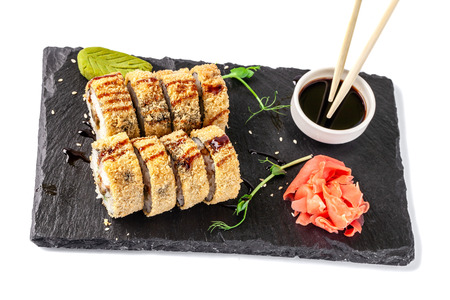 Concept of Japanese cuisine. fried roll in deep-fried Banzai with eel, cucumber. Near soy sauce, ginger and wasabi. Modern serving dishes in the restaurant on a black slate blackboard. isolated on a white background Reklamní fotografie