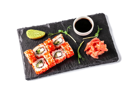 Concept of Japanese cuisine. Roll with crab sticks, cucumber and celery, with red caviar. Near soy sauce, ginger and wasabi. Modern serving dishes in the restaurant on a black slate blackboard. Фото со стока