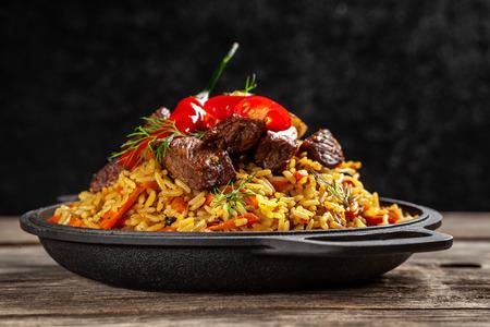 Das Konzept der orientalischen Küche. Nationaler usbekischer Pilaw mit Fleisch in einer gusseisernen Pfanne auf einem Holztisch. Hintergrundbild. Ansicht von oben, Textfreiraum, flache Lage