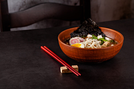 Concept of Asian cuisine. Japanese ramen soup with noodles, egg, tofu, nori, in a Japanese dish. close-up. copy space