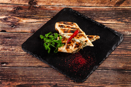 The concept of Georgian cuisine. Baked pita with suluguni cheese and cilantro. Serving dishes on a black stone slate. On a wooden background. copy space Stock Photo
