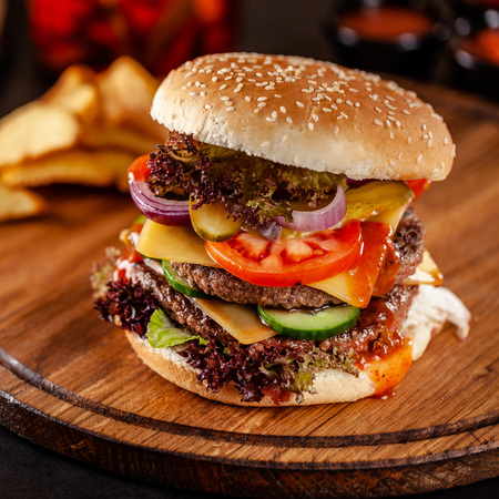 American cuisine concept. A large homemade burger with a double pork and veal meat patty, tomato, cucumber, lettuce, and cheese. Closeup, background image