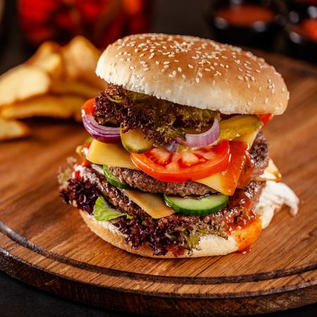 Konzept der amerikanischen Küche. Ein großer hausgemachter Burger mit einem doppelten Schweine- und Kalbfleisch-Patty, Tomate, Gurke, Salat und Käse. Nahaufnahme, Hintergrundbild
