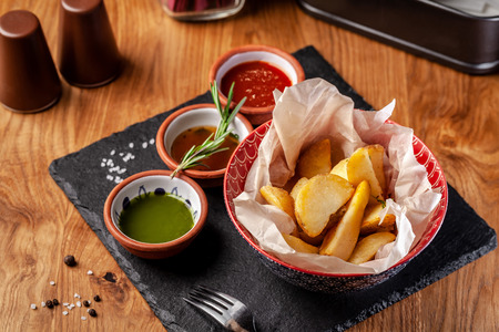 The concept of Mexican cuisine. Baked spicy potatoes with pepper, with different sauces, salsa, guacamole, chilli and shrimp. Background image. copy space