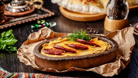 Traditional Turkish, Arabic cuisine. Hummus with salami sausage, in a clay plate, with parchment on a wood table. Serving dishes in the restaurant. copy space