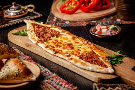 Traditional Turkish cuisine. Turkish pizza Pita with a different stuffing, meat, cheese, slices of veal. Turk Pidesi or Sucuk Pide. Serving dishes in the restaurant. Copy space