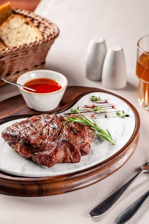American cuisine concept. Pork steak with red tomato barbecue sauce. Serving dishes on a wooden board in a restaurant. Background image. copy space