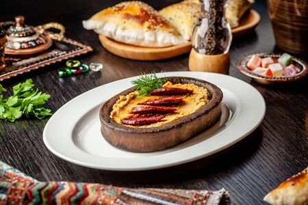 Traditional Turkish, Arabic cuisine. Hummus with salami sausage, in a clay plate, on a wood table. On a white plate. Serving dishes in the restaurant. copy space