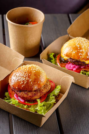Street food. Meat cutlet burgers are in paper boxes. Food delivery. Foto de archivo
