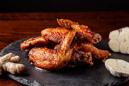 American cuisine. Fried chicken wings glazed in marinated with ginger and garlic on a black background. background image, copy space text.