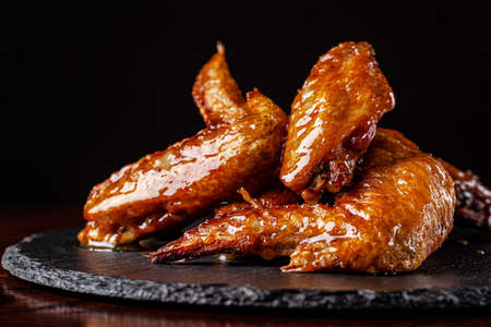 American cuisine. Fried chicken wings glazed in honey sauce on a black background. background image, copy space text