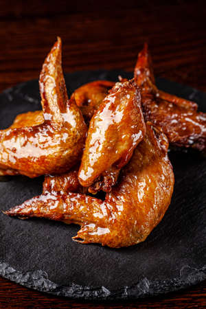 American cuisine. Fried chicken wings glazed in honey sauce on a black background. background image, copy space text Stok Fotoğraf