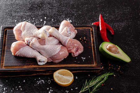 Raw meat. Chicken legs lie on a wooden board with vegetables and spices on a black background. background image, copy space text Stok Fotoğraf