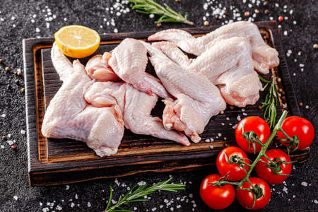 Raw meat. Chicken wings lie on a wooden board with vegetables and spices on a black background. background image, copy space text Stok Fotoğraf