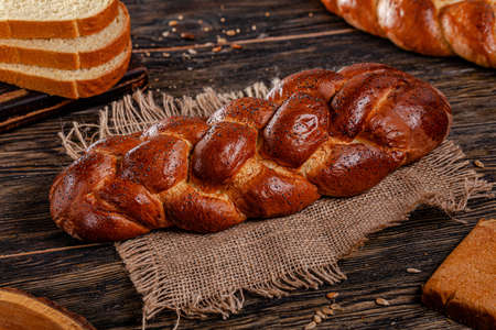 Assorted bread for catalan shooting. Long loaf, buns, baguette, pigtail, shaped. Bread on a wooden background. Stok Fotoğraf