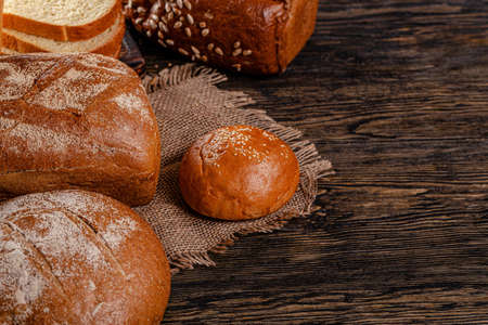 Assorted bread for catalan shooting. Long loaf, buns, baguette, pigtail, shaped. Bread on a wooden background. background image, copy space text Stok Fotoğraf