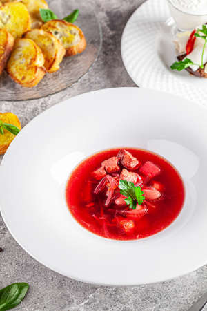 Modern Ukrainian cuisine in European style. Borsch soup with meat and sour cream. Beautiful serving dish in a restaurant in a white plate. background image, copy space text