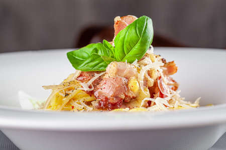Italian Cuisine. Carbanara pasta with bacon and parmesan. Beautiful serving dish in a restaurant in a white plate. background image, copy space text
