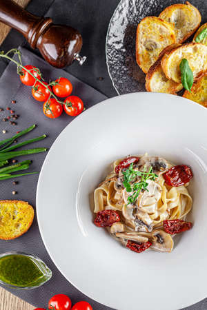 Italian cuisine. Pasta with mushrooms and sun-dried tomatoes with cream cheese sauce. Beautiful serving dish in a restaurant in a white plate. background image, copy space text
