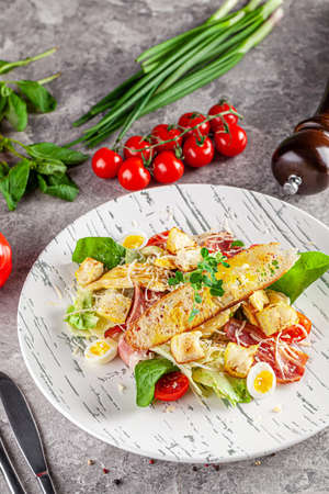 Italian Cuisine. Caesar salad with chicken, bacon, quail eggs, bread croutons, cherry tomatoes. Dish in a restaurant on a white plate. background image, copy space text