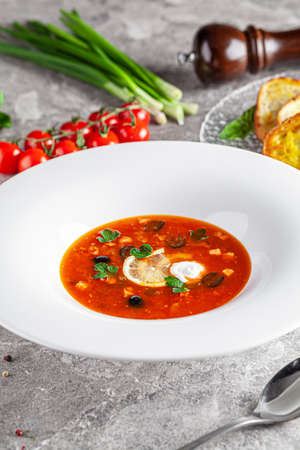 Ukrainian cuisine in European style. Solyanka soup with assorted sausages and meat. Beautiful serving dish in a restaurant in a white plate. background image, copy space text