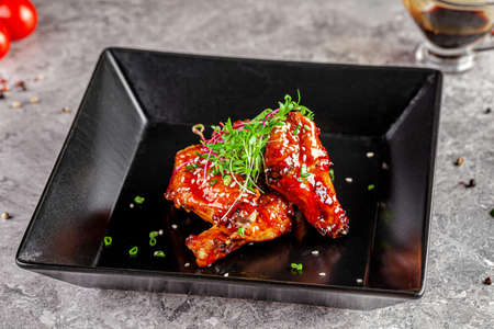 American cuisine. Juicy fried chicken wings glazed with sesame seeds and herbs. Beautiful serving dish in a restaurant in a black plate. background image, copy space text Stok Fotoğraf