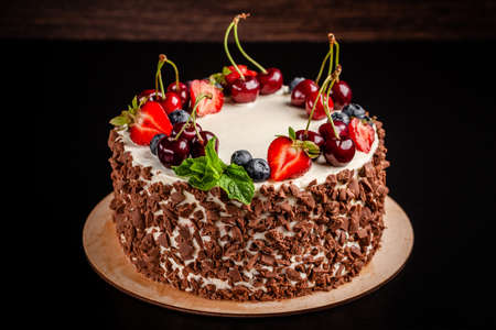 Chocolate sponge cake with white cream and berries, strawberries, cherries and mint. Cake cutaway on cinnamon background. copy space