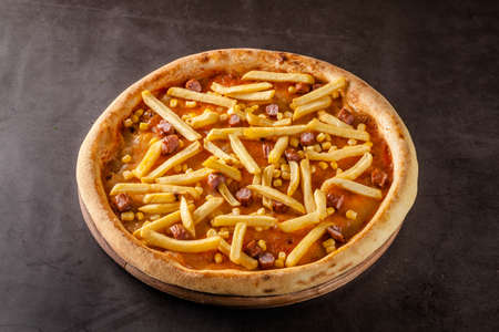 Italian Cuisine. Thin Oktoberfest pizza with french fries, hunting sausages and corn. Background image. copy space Stok Fotoğraf