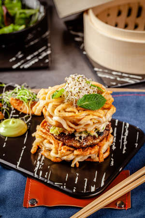Pan-Asian cuisine concept. Ramen Chinese rice noodle burger, chicken and pork cutlet and salad, with wasabi sauce. Background image. Serving dishes with french fries. copy space Stok Fotoğraf